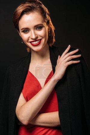 attraktives lächelndes Mädchen in rotem Kleid und schwarzer Jacke, das isoliert auf schwarz in die Kamera blickt