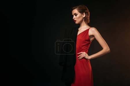 attractive girl in red dress and black jacket standing isolated on black