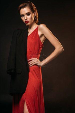 Photo pour Jolie fille en robe rouge et une veste noire sur une épaule, regardant la caméra isolée sur fond noir - image libre de droit