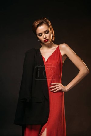 Photo for Attractive girl in red dress and black jacket on one shoulder looking down isolated on black - Royalty Free Image