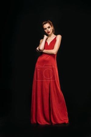 Photo pour Vue faible angle de jolie fille en robe rouge et veste noire, regardant la caméra isolée sur fond noir - image libre de droit