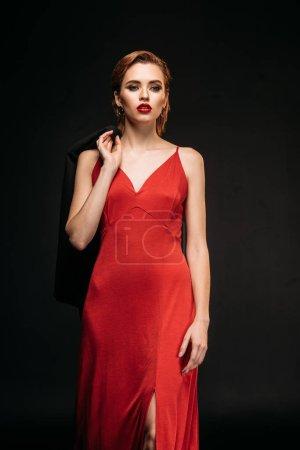 Photo pour Jolie fille en robe rouge et veste noire marche isolé sur noir - image libre de droit