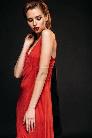 attractive girl in red dress holding black jacket and looking down isolated on black