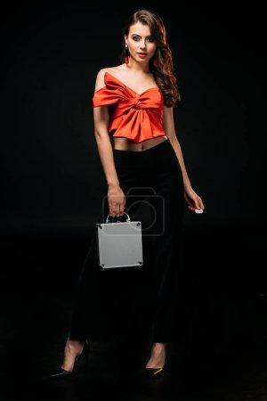 schöne braune Haare Mädchen in rotem Korsett hält Spardose und Casino-Chips isoliert auf schwarz, Blick in die Kamera