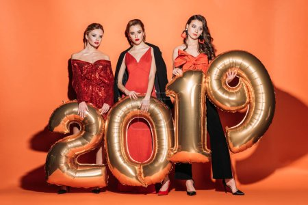 confident attractive girls in stylish party clothes holding 2019 balloons on orange