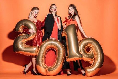 Photo pour Heureuse jolies filles en vêtements élégant partie posant avec golden 2019 ballons sur orange - image libre de droit