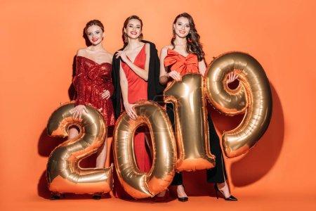 Photo pour Jolies filles en vêtements élégants parti détenant 2019 en souriant et regardant les ballons de la caméra sur orange - image libre de droit