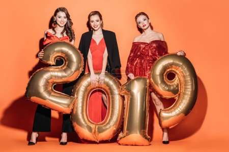 Photo for Happy beautiful girls in fashionable party clothes holding golden 2019 balloons on orange, new year concept - Royalty Free Image