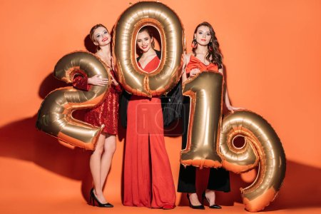 Photo pour Sourire des jolies filles dans des vêtements de mode partie posant avec des ballons de 2019 sur orange - image libre de droit