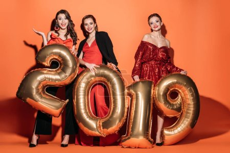 Photo for Surprised attractive girls in stylish party clothes holding 2019 balloons and looking at camera on orange - Royalty Free Image