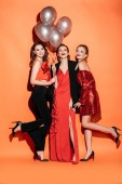 laughing attractive girls in stylish party clothes holding bundle of grey balloons on orange