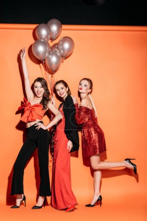 Photo for Happy attractive girls in stylish party clothes holding bundle of grey balloons and posing on orange - Royalty Free Image