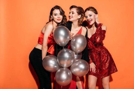 Photo pour Riant jolies filles dans des vêtements de fête élégants tenant paquet de ballons gris isolé sur orange - image libre de droit