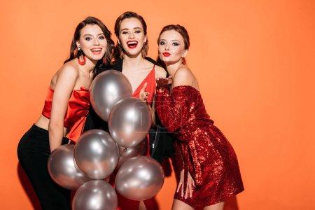 Foto de Risa a chicas guapas en ropa elegante fiesta celebración de manojo de Globos gris y mirando a cámara aislada en naranja - Imagen libre de derechos