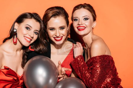 portrait of smiling attractive girls in stylish party clothes with bundle of grey balloons isolated on orange