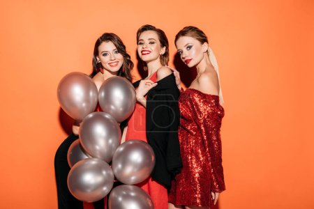 Photo for Happy attractive girls in fashionable party clothes holding bundle of grey balloons and looking at camera isolated on orange - Royalty Free Image