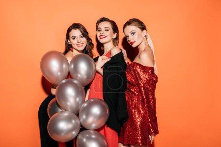 Foto de Felizes chicas atractivas en ropa de fiesta moda holding paquete de Globos gris y mirando a cámara aislada en naranja - Imagen libre de derechos