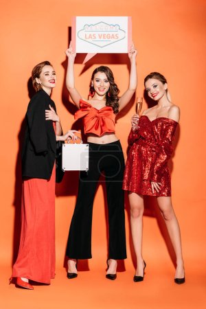 Photo for Smiling attractive girls in stylish party clothes holding welcome las vegas sign and cash box isolated on orange - Royalty Free Image