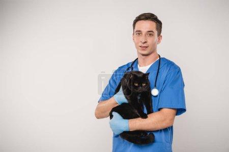 schöner Tierarzt mit schwarzer Katze auf grauem Hintergrund