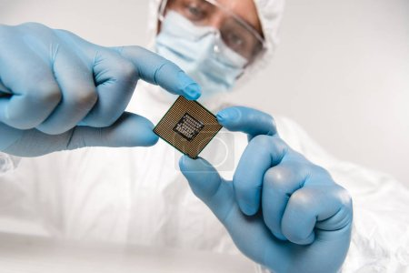 selective focus of microchip in hands of scientist wearing latex gloves, googles and mask on grey background