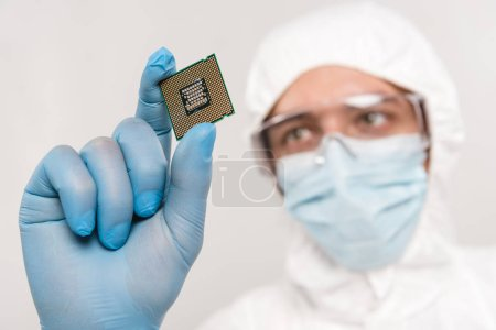 selective focus of microchip in hand of scientist wearing latex glove and googles isolated on grey