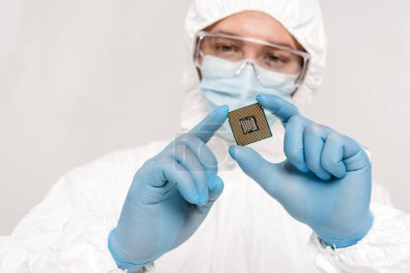 selective focus of microchip in hands of scientist wearing latex gloves and googles isolated on grey