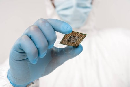 selective focus of microprocessor in hand of scientist wearing latex glove isolated on grey