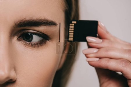 cropped view of woman inserting microchip in head