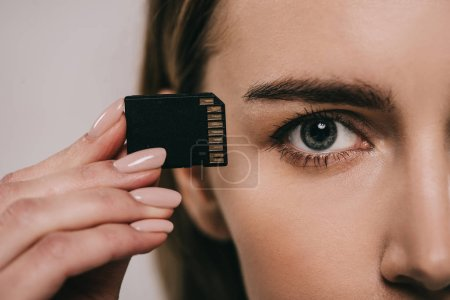 Photo for Cropped view of woman holding microchip in hand near eye - Royalty Free Image