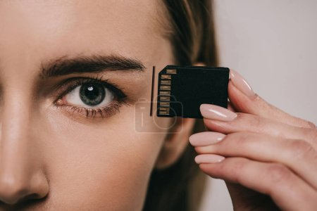cropped view of woman holding microchip while inserting in head