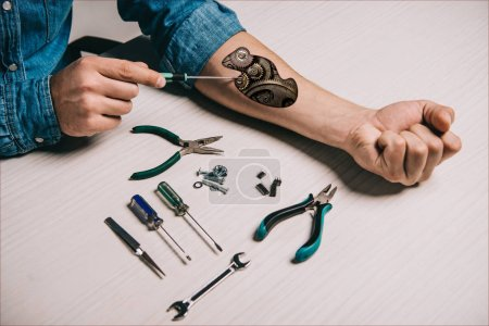 Photo for Cropped view of man repairing metallic mechanism in arm with screwdriver - Royalty Free Image