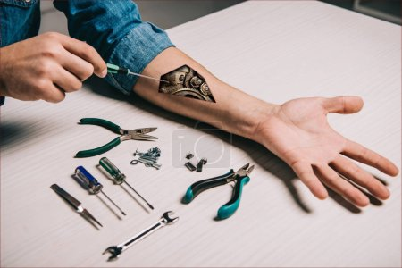 Photo for Cropped view of man repairing metallic mechanism in arm with wrench and pliers - Royalty Free Image