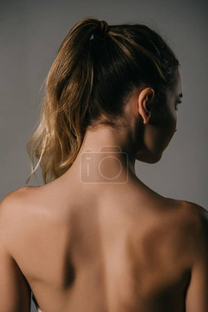 back view of girl with ponytail on grey background