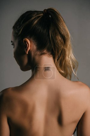 back view of blonde woman with barcode on neck on grey background