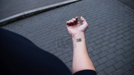 Photo for Cropped view of man with barcode on hand with bricks on background - Royalty Free Image