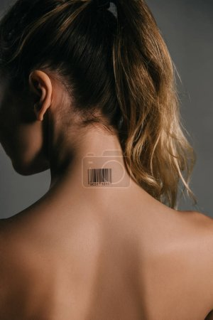back view of woman with coded barcode on neck on grey background