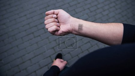 cropped view of barcode on male hand  with bricks on background
