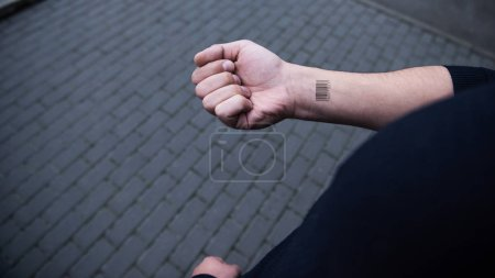 cropped view of male hand with barcode with bricks on background