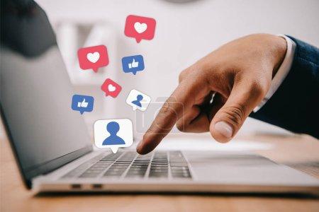 Photo pour Vue partielle de l'homme d'affaires tapant sur ordinateur portable sur le lieu de travail avec des icônes multimédia - image libre de droit