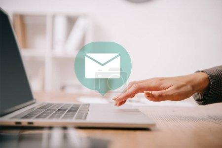 Photo pour Recadrée vue de femme d'affaires, dactylographie sur ordinateur portable au lieu de travail avec l'icône d'e-mail - image libre de droit