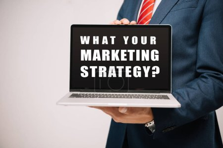 cropped view of businessman in suit presenting laptop with what your marketing strategy? isolated on grey