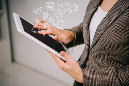 cropped view on businesswoman using and touching digital tablet with seo icons