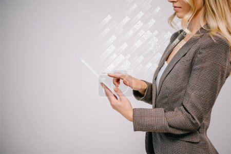 Photo for Cropped view on businesswoman in suit touching digital tablet with sending e-mails icons isolated on grey - Royalty Free Image