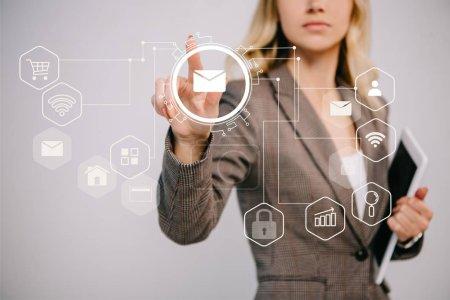 Photo pour Recadrée vue sur la femme d'affaires en costume tenant la tablette numérique et pointant à icônes de marketing par courriel - image libre de droit