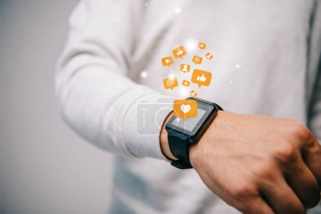 cropped view of man with smartwatch with multimedia icons