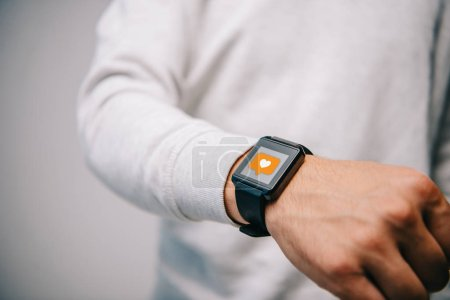 Photo for Cropped view of man with smartwatch with multimedia like icon - Royalty Free Image