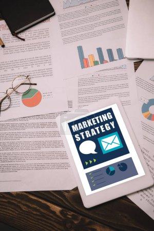 Photo pour Vue de dessus de tablette numérique avec les documents de stratégie et de marketing - image libre de droit