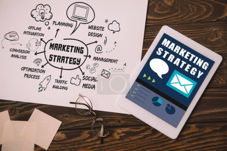 top view of digital tablet and paper with marketing strategy on wooden table