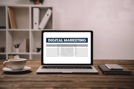 laptop with digital marketing, smartphone and cup of coffee on wooden table