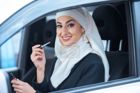 beautiful smiling young muslim woman sitting in car and holding lip gloss